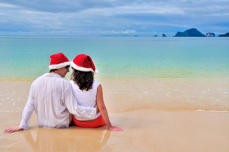 Lyckliga par i jultomtenhattar som kopplar av på den tropiska sandiga stranden nära havet, ferie för jul och för nytt år, semestr royaltyfri fotografi