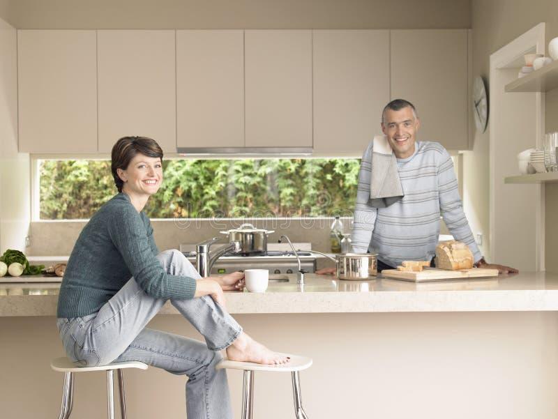 Lyckliga par i kök arkivbild