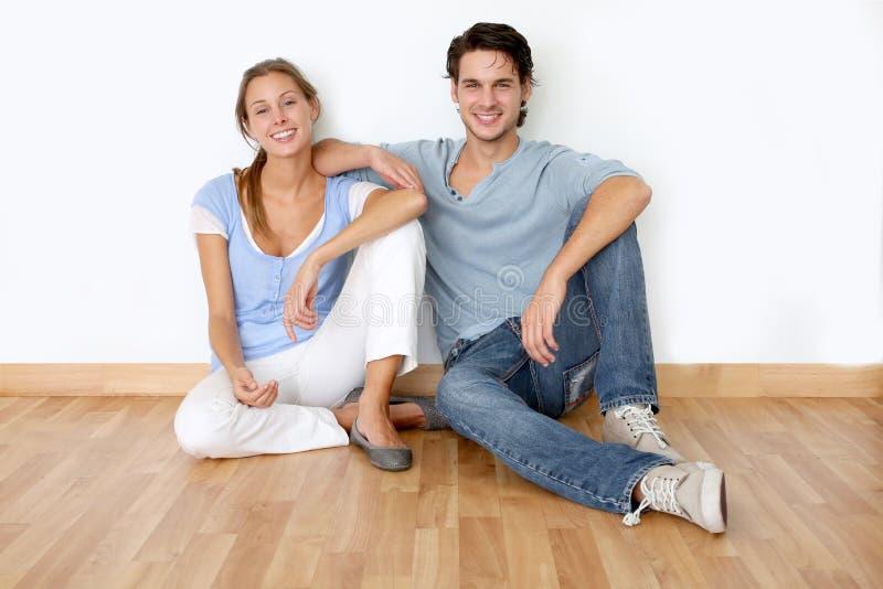 Lyckliga par i lägenhet royaltyfri bild