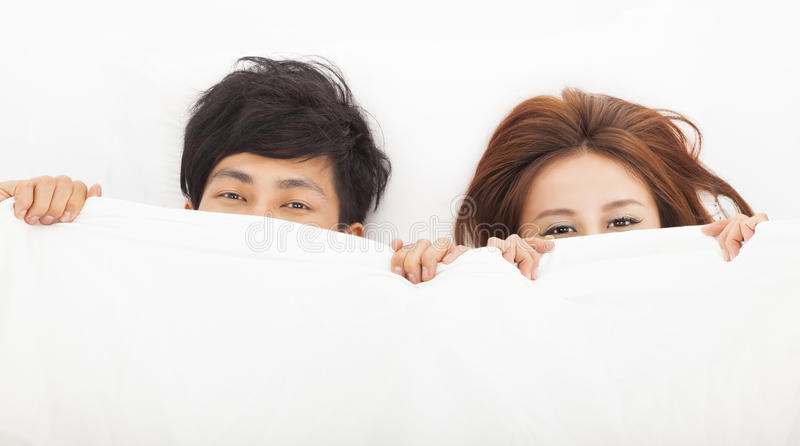 lyckliga par i säng royaltyfria foton