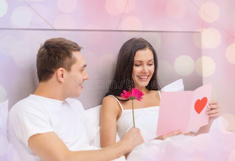 Lyckliga par i säng med vykortet och blomman royaltyfri bild
