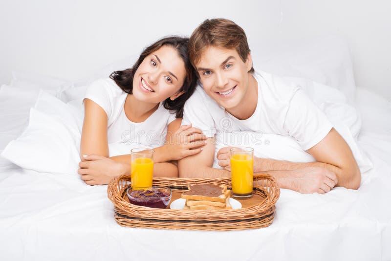 Lyckliga par i säng som har frukosten arkivbild