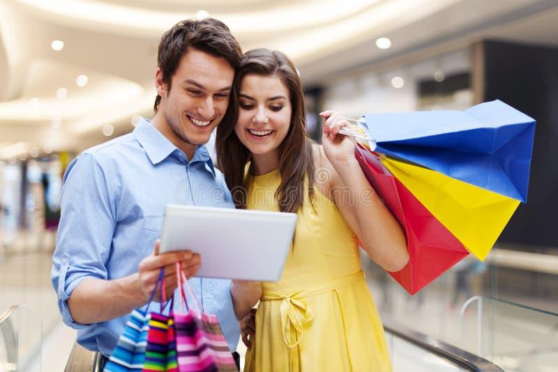 Lyckliga par i shoppinggalleria fotografering för bildbyråer