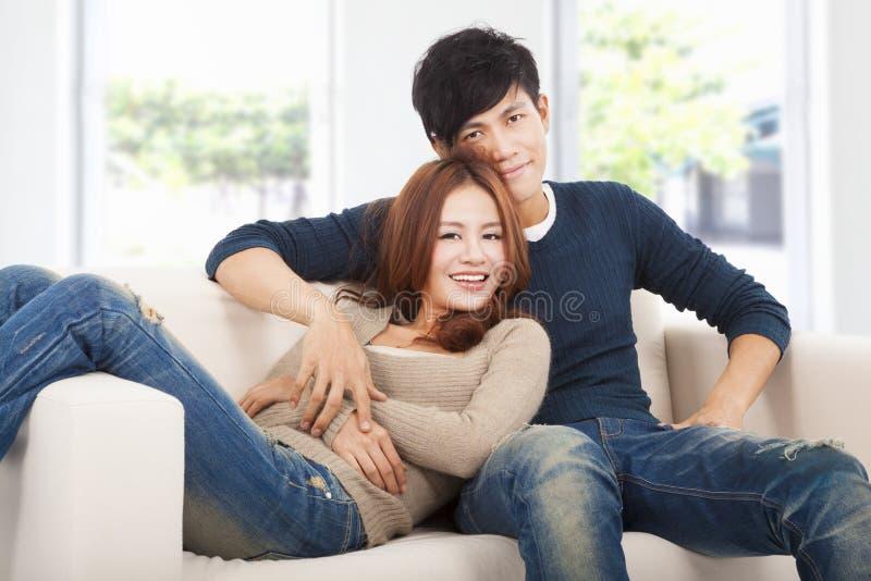 Lyckliga par i soffa hemma royaltyfri bild