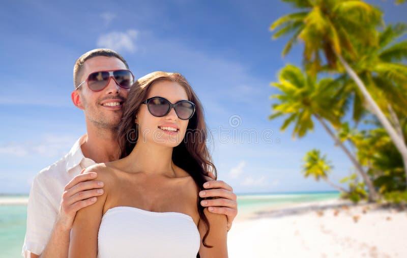 Lyckliga par i solglasögon över den tropiska stranden arkivbild