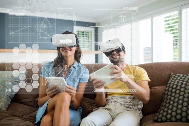 Lyckliga par i VR-hörlurar med mikrofon som ser manöverenheten royaltyfri bild