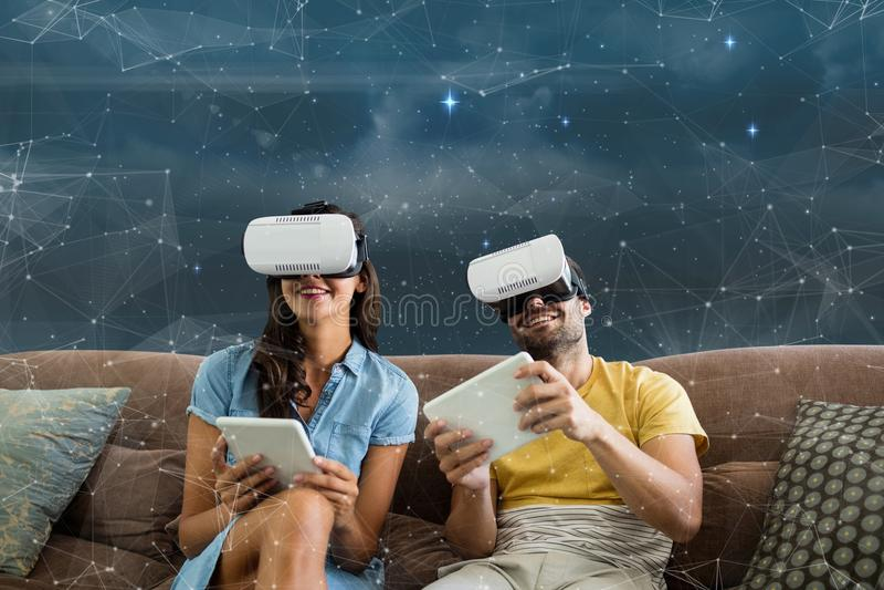 Lyckliga par i VR-hörlurar med mikrofon som sitter mot galaxbakgrund arkivfoton