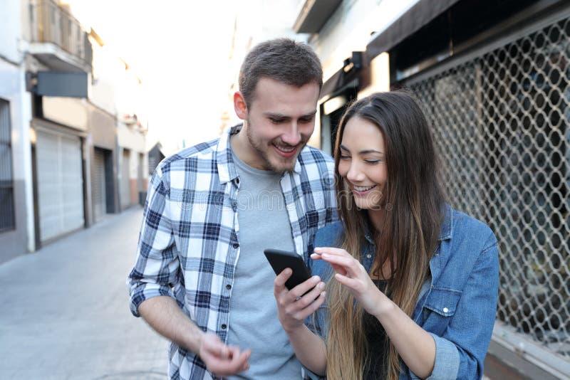 Lyckliga par kontrollerar det smarta telefoninnehållet i gatan royaltyfri fotografi