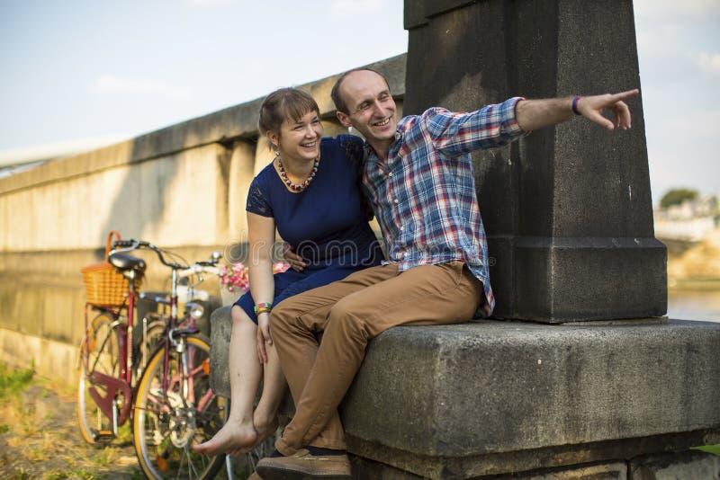 lyckliga par Koppla ihop förälskat talande känslomässigt sammanträde på den stads- stenstranden fotografering för bildbyråer