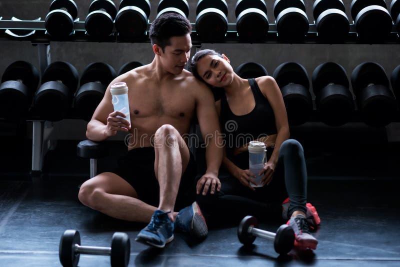 Lyckliga par kopplar av efter övning i idrottshall royaltyfri bild
