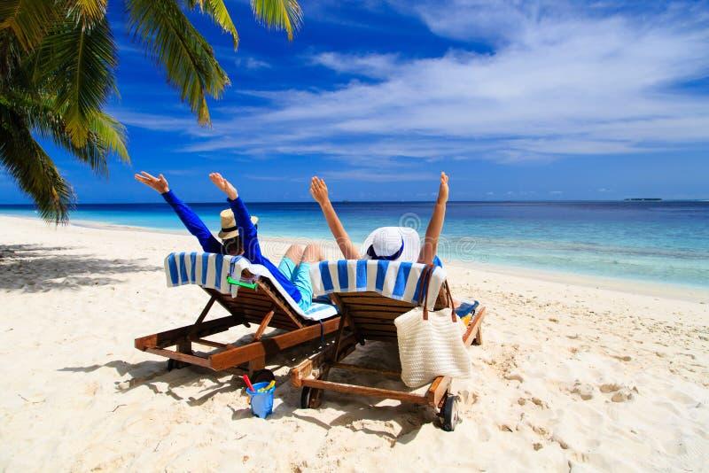 Lyckliga par kopplar av på en tropisk strand arkivfoton