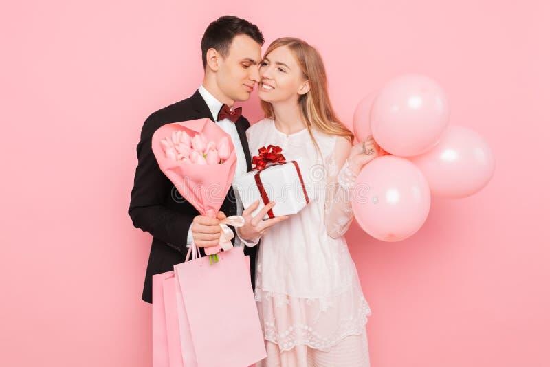 Lyckliga par, man och kvinna, med en gåva och en bukett av blommor, med påsar, når att ha shoppat, på en rosa bakgrund royaltyfri foto