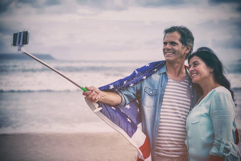 Lyckliga par med amerikanska flaggan som tar selfie royaltyfri bild