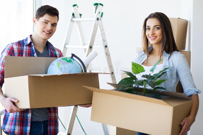 Lyckliga par med askar som flyttar sig till det nya hemmet arkivfoto