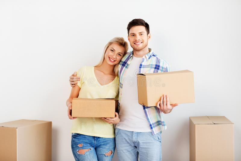 Lyckliga par med askar som flyttar sig till det nya hemmet royaltyfri foto