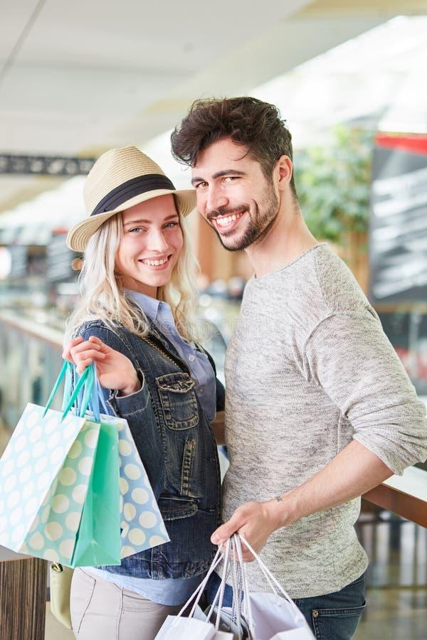 Lyckliga par med att shoppa för många påsar royaltyfri foto