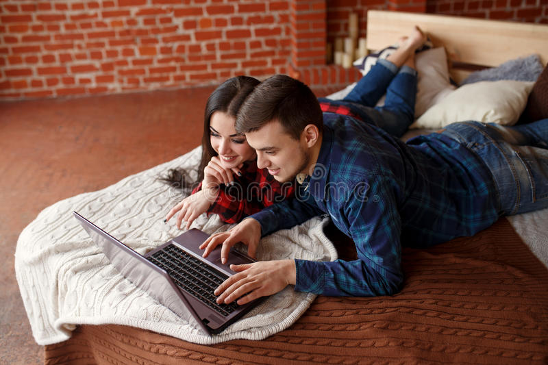 Lyckliga par med bärbara datorn som direktanslutet hemma shoppar, bläddrar internet i säng, ler och har gyckel royaltyfri foto
