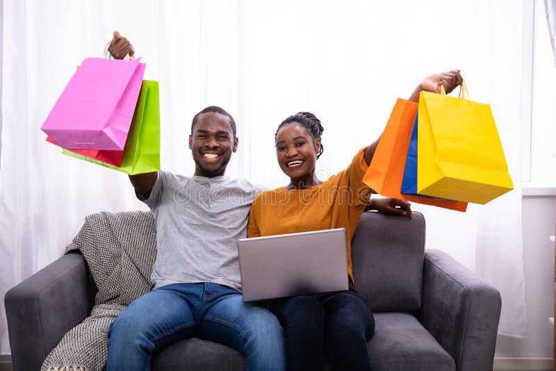 Lyckliga par med b?rbara datorn som rymmer f?rgrika shoppa p?sar royaltyfri fotografi