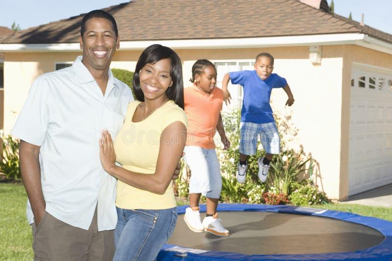 Lyckliga par med barn som spelar på trampolinen arkivbild