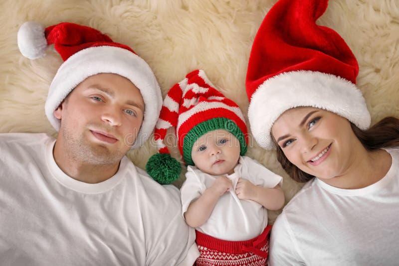 Lyckliga par med behandla som ett barn i julhattar på den luddiga filten, bästa sikt arkivfoton