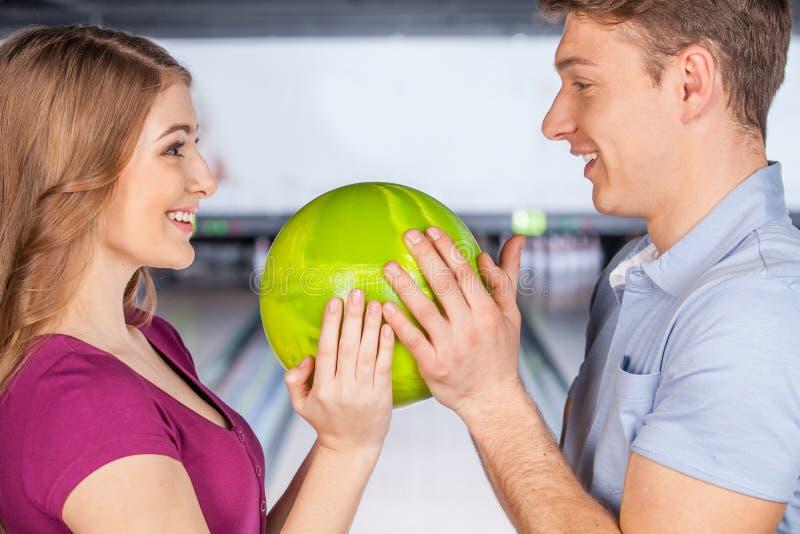 Lyckliga par med bowlingklot. arkivfoto