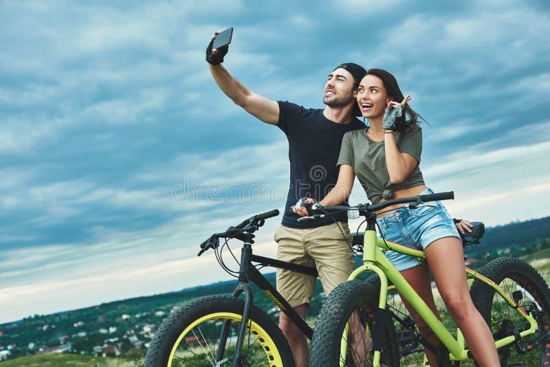 Lyckliga par med cykeln som utomhus tar selfie vid smartphonen fotografering för bildbyråer
