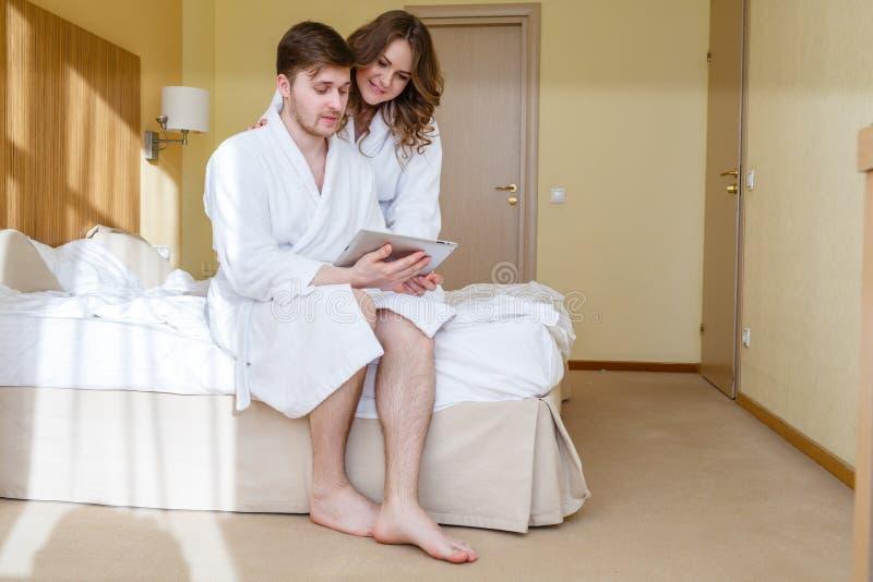 Lyckliga par med datorminnestavlan royaltyfria foton