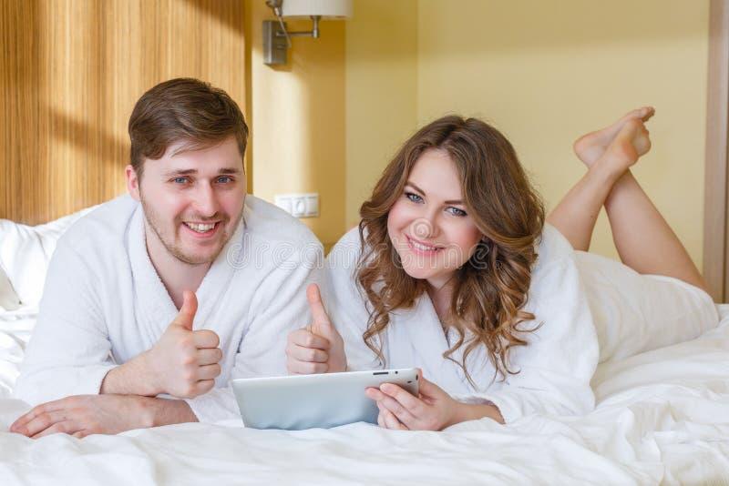 Lyckliga par med datorminnestavlan arkivfoton