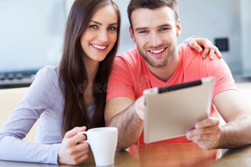 Lyckliga par med den digitala minnestavlan fotografering för bildbyråer