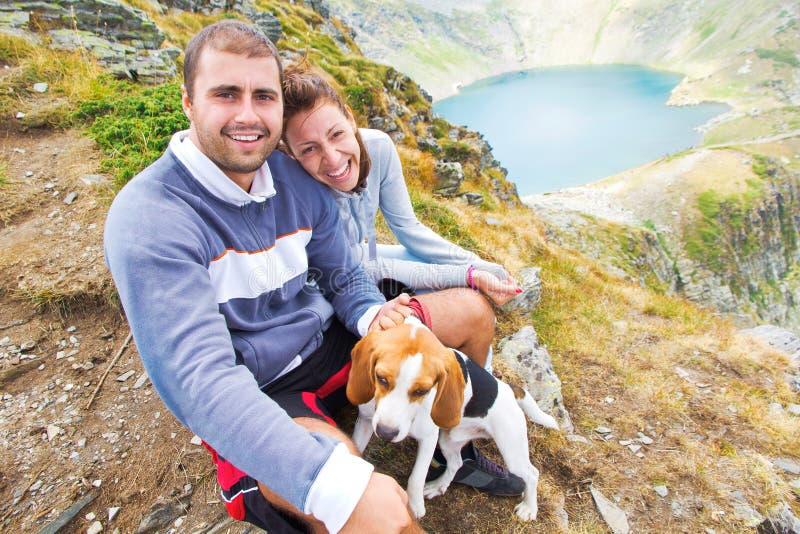 Lyckliga par med deras hund i bergen royaltyfria bilder