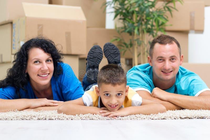 Lyckliga par med en unge i deras nya hem som lägger på golvwina royaltyfria bilder