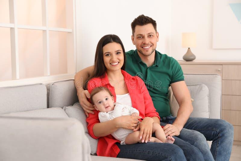 Lyckliga par med f?rtjusande behandla som ett barn p? soffan Familj Tid royaltyfria foton