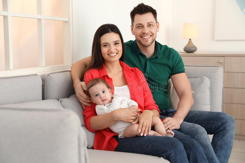 Lyckliga par med f?rtjusande behandla som ett barn p? soffan hemma royaltyfri bild