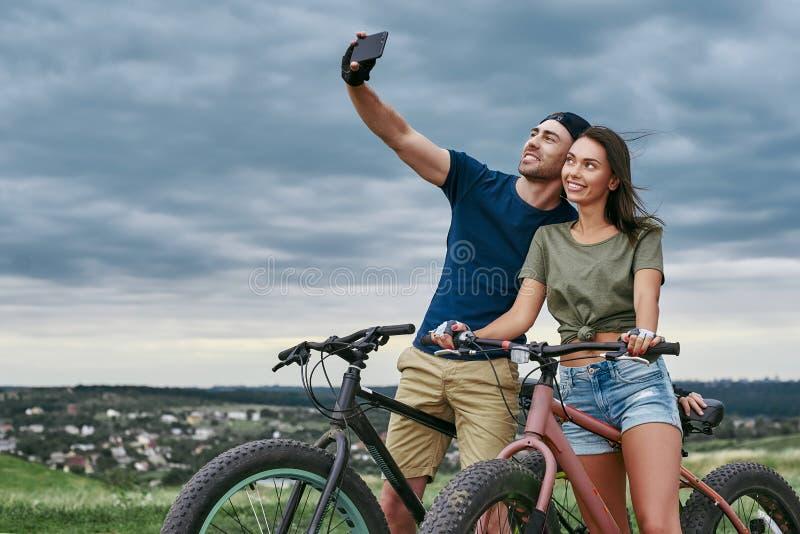 Lyckliga par med fatbikes som utomhus tar selfie vid smartphonen fotografering för bildbyråer