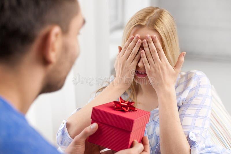 Lyckliga par med gåvaasken hemma arkivbild