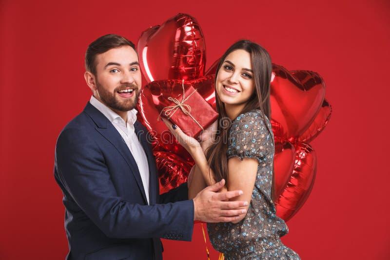 Lyckliga par med gåvan och ballonger på en röd bakgrund royaltyfri foto