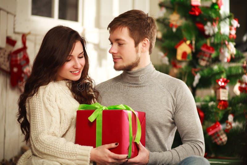 Lyckliga par med gåvan som är hemmastadd på bakgrund av julgranen arkivfoto