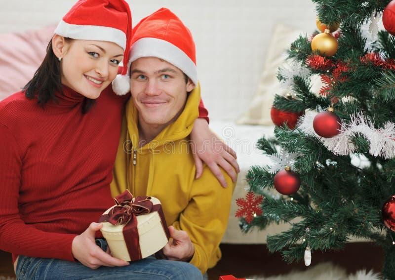 Lyckliga par med gåvan som sitter nära julgran arkivfoton