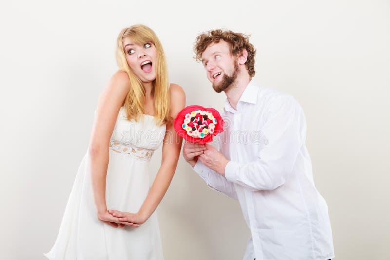 Lyckliga par med godisgruppblommor Förälskelse arkivfoton