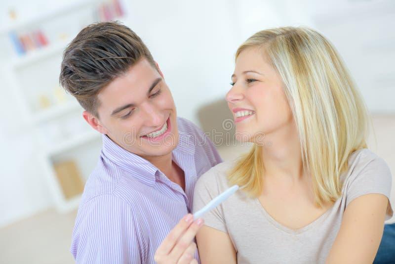 Lyckliga par med graviditetstestet arkivfoton