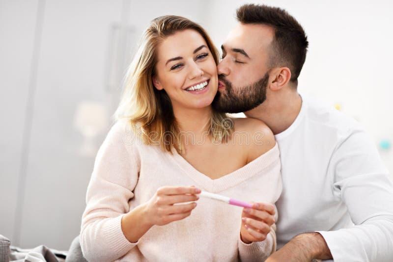 Lyckliga par med graviditetstestet i sovrum arkivbilder