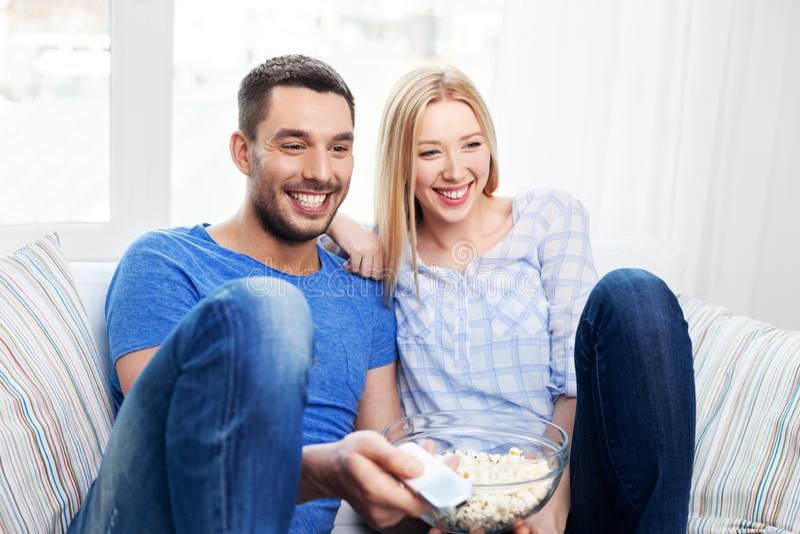 Lyckliga par med hållande ögonen på tv för popcorn hemma arkivfoto