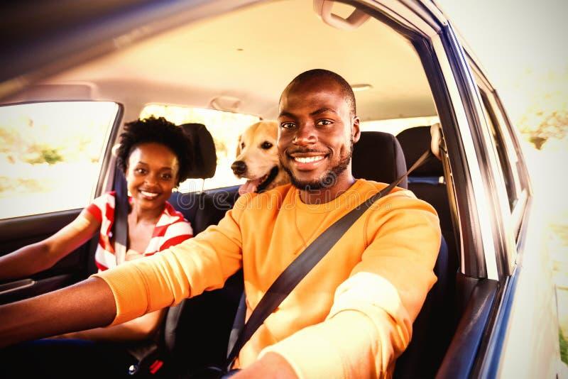 Lyckliga par med hunden som sitter i bil royaltyfri foto
