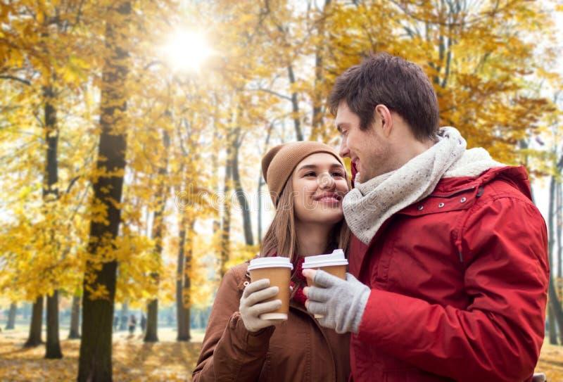 Lyckliga par med kaffe som g?r i h?st, parkerar arkivfoto