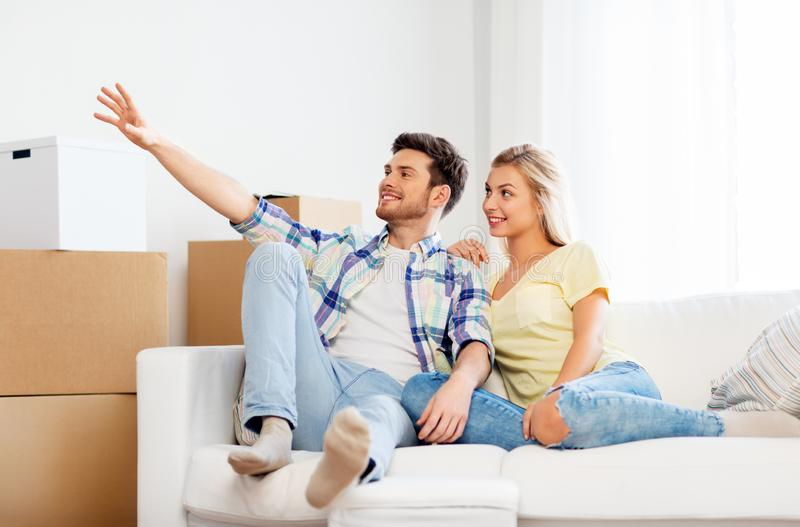 Lyckliga par med kartonger på det nya hemmet fotografering för bildbyråer