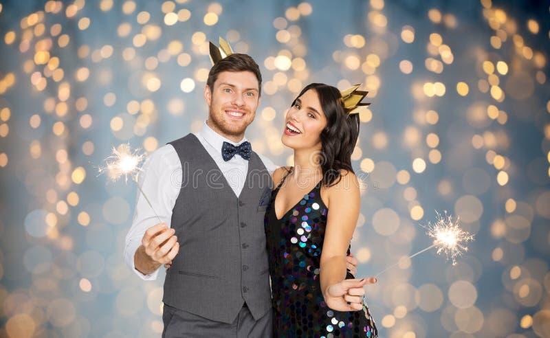 Lyckliga par med kronor och tomtebloss på partiet arkivfoton