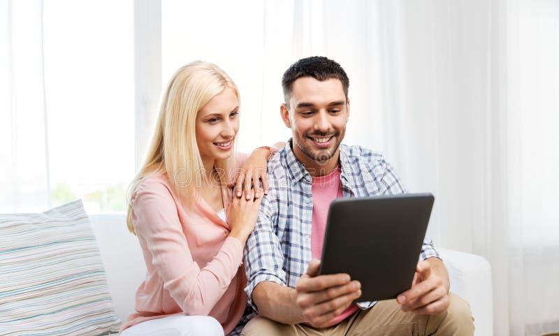 Lyckliga par med minnestavladatoren hemma fotografering för bildbyråer