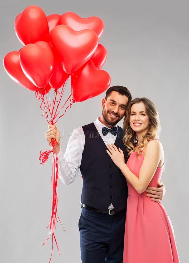 Lyckliga par med röd hjärta formade ballonger royaltyfria bilder