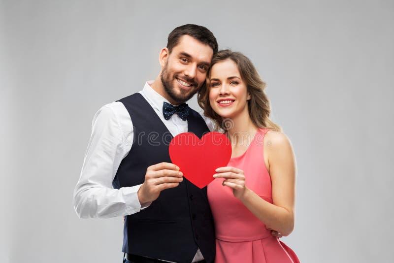 Lyckliga par med röd hjärta på valentindag royaltyfria foton