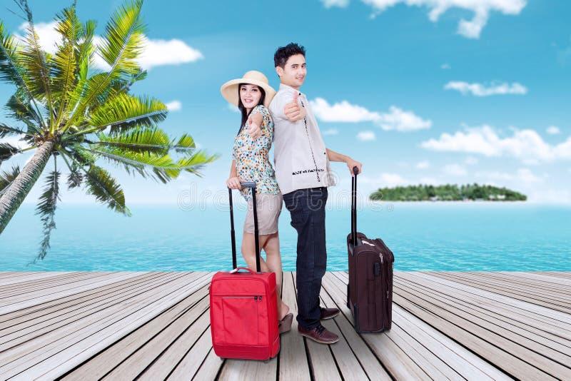 Lyckliga par med resväskan på pir royaltyfri bild